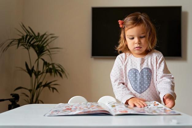 Atividade de livro infantil em casa para design de jogos. criança feliz e inteligente. juventude e educação. garoto da escola em casa. vista do topo.