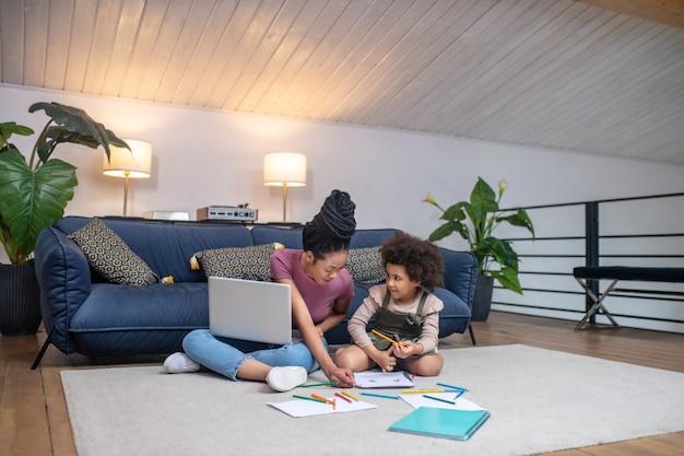 Atividade interessante. mulher de pele muito escura atenciosa com laptop ajudando a desenhar uma menina sentada no chão em um quarto aconchegante