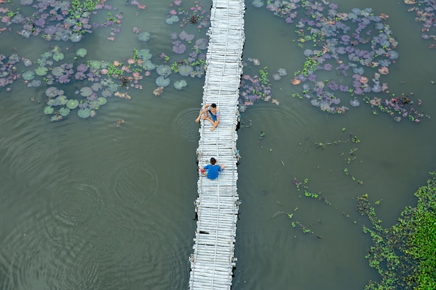 Atividade tailandesa da infância ao lado da lagoa de lótus.