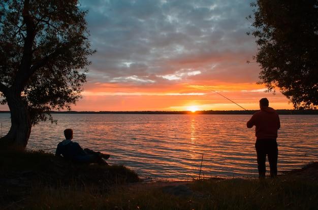 Atividades ao ar livre. silhueta de um pescador e seu amigo no lago ao pôr do sol. homem descansando na costa, pescador pegando peixes. paisagem do pôr do sol