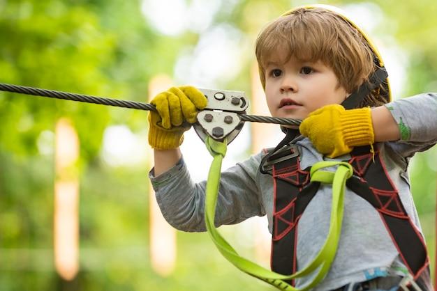 Atividades infantis de verão. retrato de uma linda criança em um parque de corda entre as árvores. toda infância