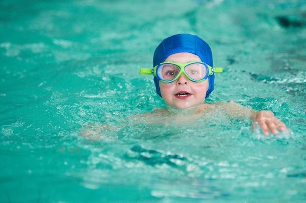 Atividades na piscina, crianças nadando e brincando na água