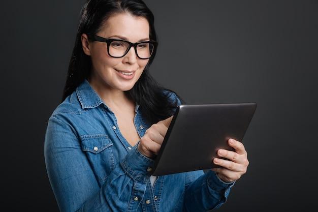 Atividades online. doce e atenciosa senhora atraente usando seu tablet para fazer compras em pé, isolado em um fundo cinza