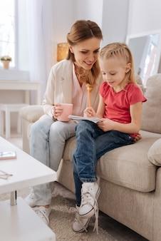 Atividades pré-escolares. mulher jovem e alegre segurando uma xícara de chá e sorrindo enquanto olha para as anotações da filha