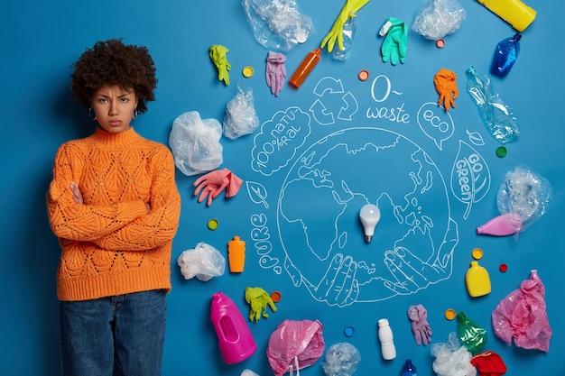 Ativista afro-americana insatisfeita em campanha antipoluição, olha furiosa para a câmera com as mãos cruzadas, posa contra um fundo azul