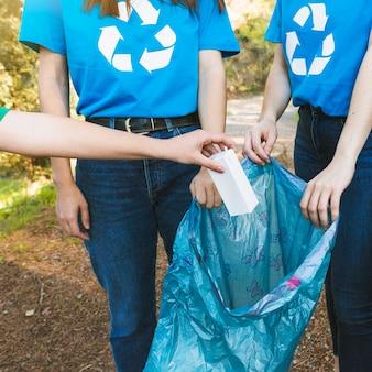 Ativistas coletando lixo de papel no saco