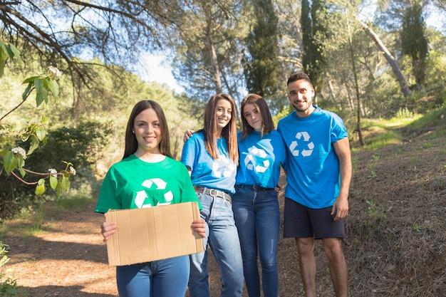 Ativistas de ecycle em pé na floresta
