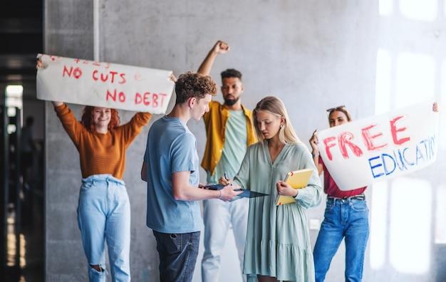 Ativistas de estudantes universitários protestando dentro de casa na escola, lutando pelo conceito de educação gratuita.