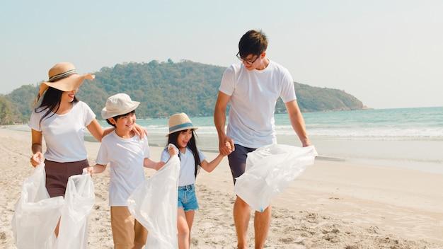 Ativistas de família felizes jovens asiáticos coletando resíduos de plástico e andando na praia. os voluntários da ásia ajudam a manter a natureza limpa o lixo. conceito sobre problemas de poluição de conservação ambiental.