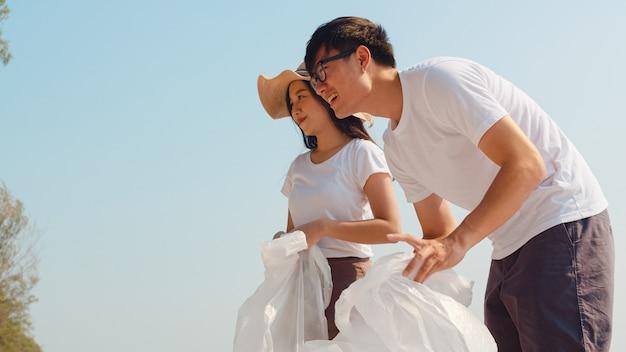 Ativistas felizes novos asiáticos da família que recolhem resíduos plásticos na praia. os voluntários da ásia ajudam a manter a natureza limpa e a recolher o lixo. conceito sobre problemas de poluição de conservação ambiental.