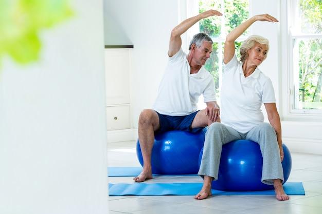 Ativo casal sênior fazendo aeróbica na bola
