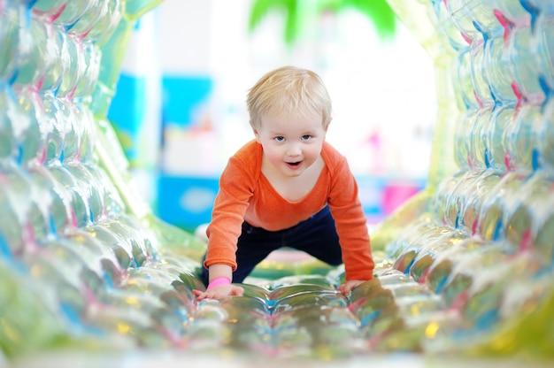 Ativo garoto feliz da criança brincando no playground dentro de casa