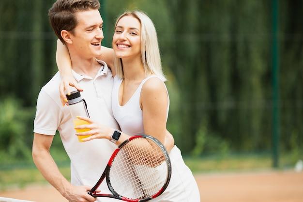 Ativo homem e mulher na quadra de tênis