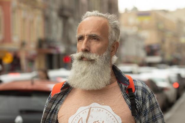 Ativo homem sênior andando na cidade. retrato do homem sênior com uma barba ao estar fora.