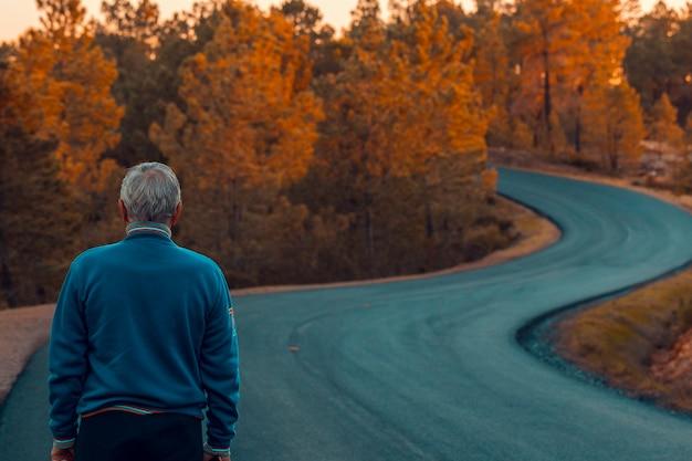 Ativo homem sênior fica sozinho na estrada solitária entre montanhas