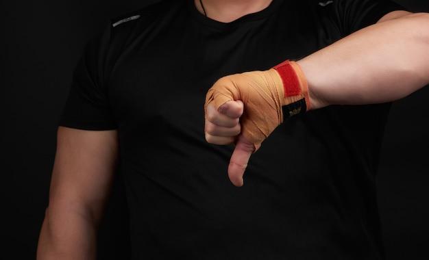 Atleta adulto de uniforme preto e mãos rebobinadas com bandagem têxtil mostra gesto de antipatia