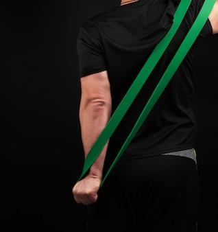 Atleta adulto de uniforme preto fica de costas e estica uma faixa elástica verde de esportes
