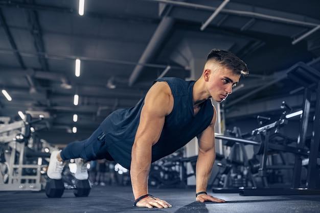 Atleta adulto jovem doing push ups como parte do treinamento de musculação.
