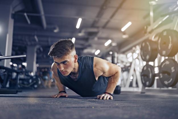 Atleta adulto jovem fazendo flexões como parte do treinamento de fisiculturismo