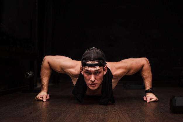 Atleta adulto jovem fazendo flexões como parte do treinamento de musculação