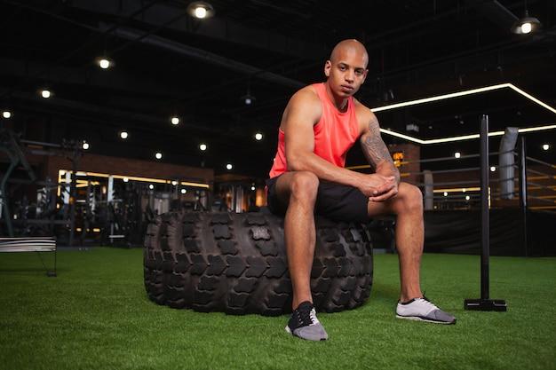 Atleta africano masculino bonito malhando na academia
