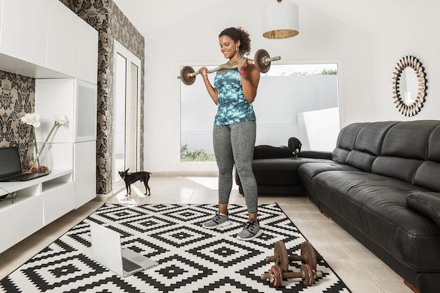 Atleta afro-americana positiva usando roupas esportivas, fazendo exercícios de rosca direta com barra e assistindo a vídeos on-line no laptop durante o treinamento na sala de estar com cães