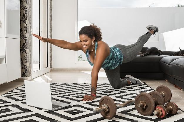 Atleta afro-americana sorridente, equilibrando-se e fazendo exercícios enquanto assiste a uma aula on-line no laptop durante o treinamento em casa
