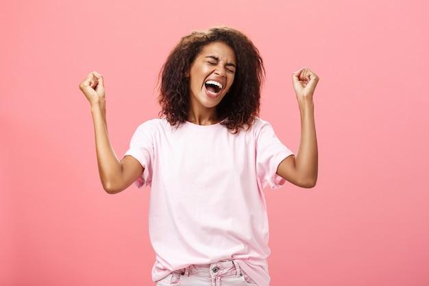 Atleta afro-americana triunfante e feliz, comemorando a vitória, gritando com sentimentos emocionantes incríveis, fechando os olhos levantando os punhos em gesto de vitória em pé sobre a parede rosa