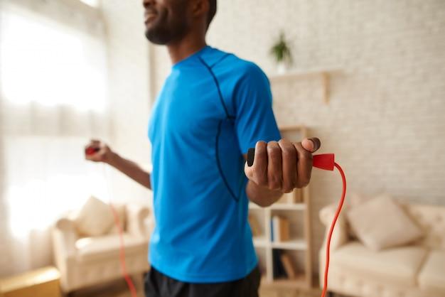 Atleta afro-americano que faz exercícios com corda de salto.