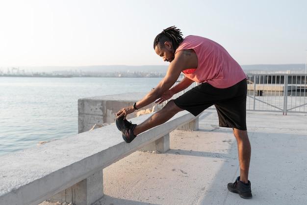 Atleta afro-americano se alongando ao ar livre