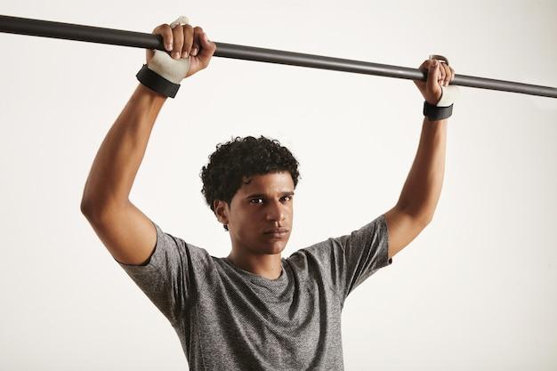 Atleta afro-americano vestindo camiseta técnica e proteção para as mãos de cross fitness segurando barra pullup de carbono isolada no branco