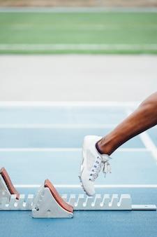 Atleta afro irreconhecível em roupas esportivas, começando a corrida agachada na posição inicial nos blocos de largada