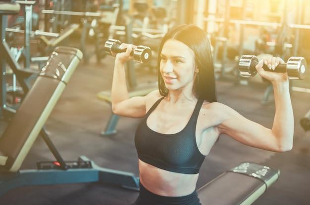 Atleta alegre mulher sorrindo e fazendo exercícios de pressão com halteres sentado no banco na academia