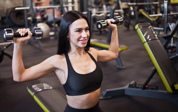 Atleta alegre mulher sorrindo e fazendo halteres pressione exercício sobre sentado no banco no ginásio