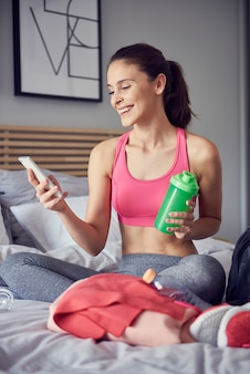 Atleta alegre usando um telefone celular no quarto