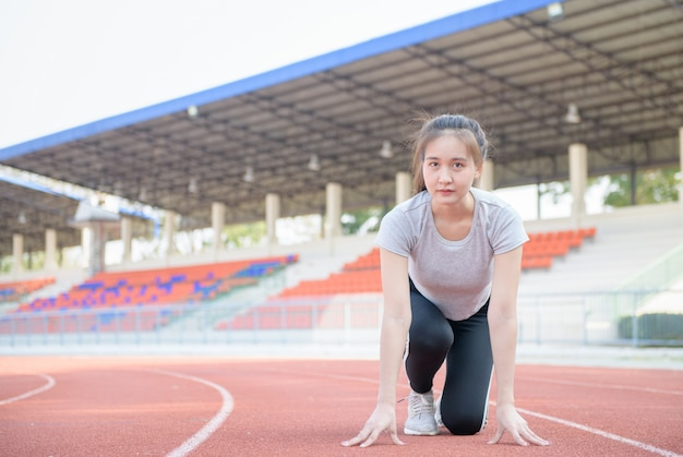 Atleta asiática bonita em uma pista de corrida está pronta para correr,