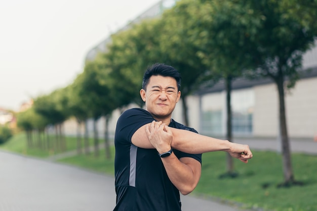 Atleta asiático, amassando dor no ombro, músculos do braço doloridos no parque