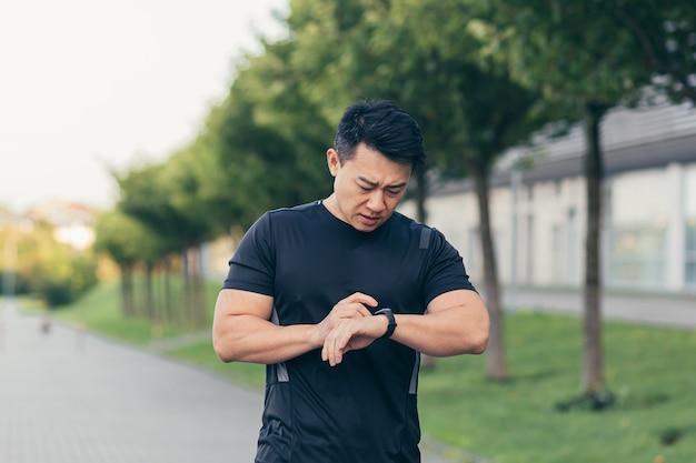 Atleta asiático, cansado depois de uma corrida matinal, corre no parque perto do estádio