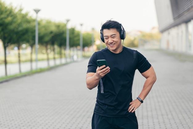 Atleta asiático em uma corrida matinal no parque perto do estádio ouve música e podcast em fones de ouvido grandes usa o telefone