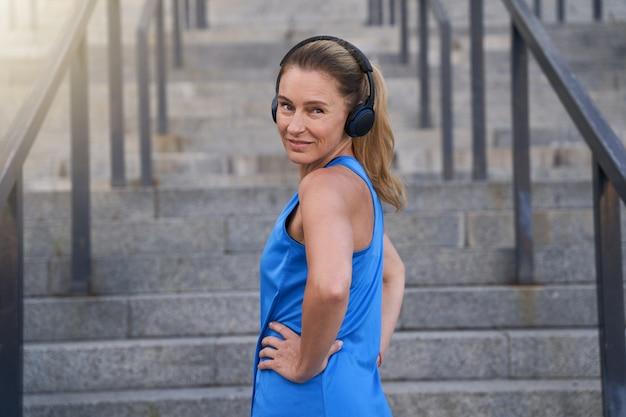 Atleta ativa em fones de ouvido, olhando para a câmera em pé com as mãos na cintura, pronta ao ar livre