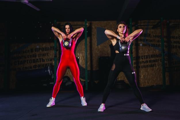 Atleta atraente duas mulheres realizando um balanço de chaleira-bell no ginásio