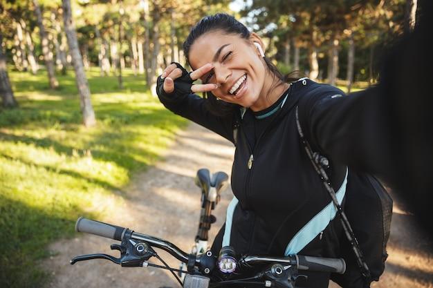 Atleta atraente em forma, andando de bicicleta no parque, ouvindo música com fones de ouvido sem fio, tirando uma selfie