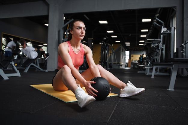 Atleta atraente fazendo abdominais com medicine ball