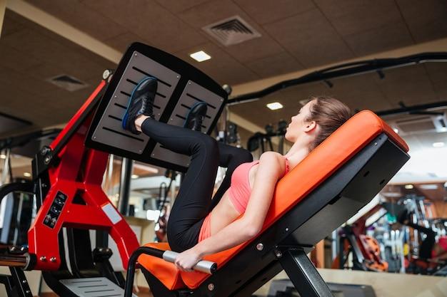 Atleta atraente jovem e séria treinando músculos das pernas na academia