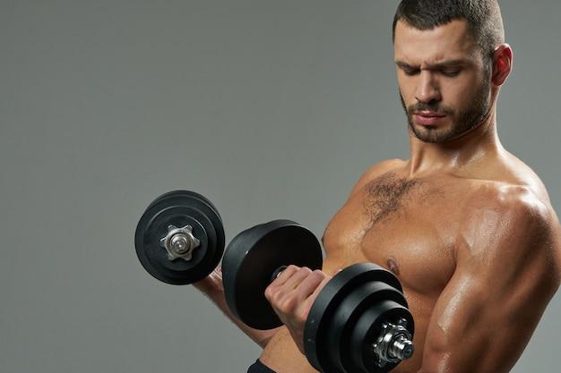 Atleta barbudo caucasiano concentrado desenvolvendo músculos com halteres em uma sala dentro de casa