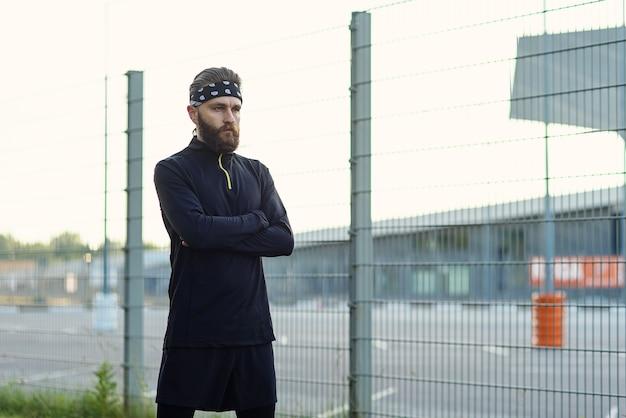 Atleta barbudo do sexo masculino com uniforme esportivo e bandana após treinamento pesado no playground
