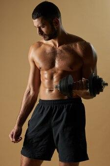 Atleta barbudo homem desenvolvendo força com ferramenta especial enquanto posa em estúdio