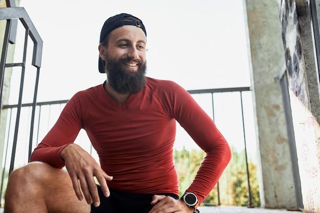 Atleta barbudo sorridente e ativo descansando e sentado na escada em um dia claro
