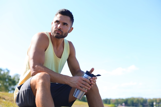 Atleta bebendo água e relaxando após intenso treino ao ar livre.