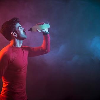 Atleta bebendo água no escuro